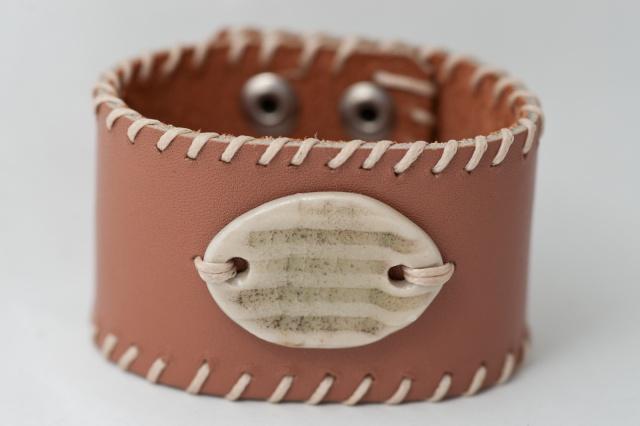Breites Armband mit Medaillon und Garn. Verschluss: Druckknöpfe Bild