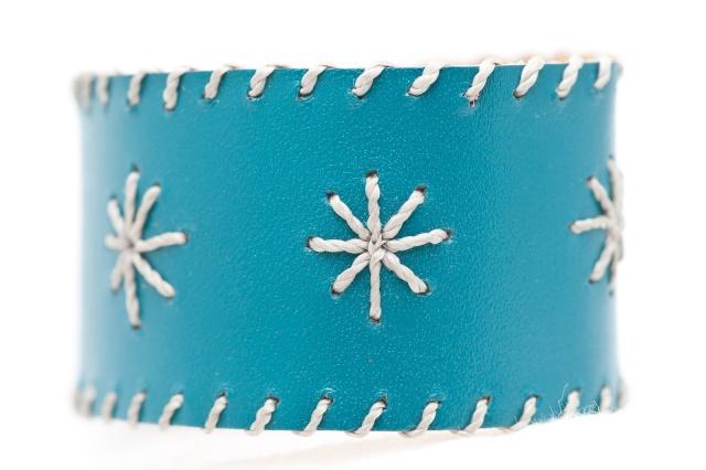 Breites Armband mit Sternen aus grauen Garn. Verschluss: Druckknöpfe Bild