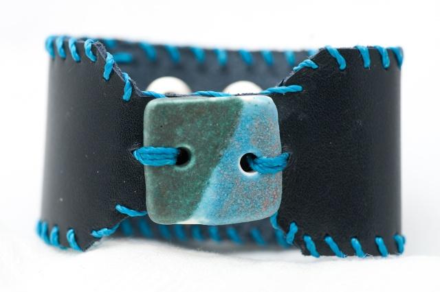 Breites Armband mit Medaillon und Garn. Verschluss: Schnalle Bild