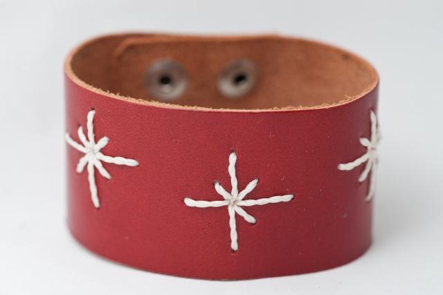 Breites Armband mit Sternen aus weißen Garn. Verschluss: Druckknöpfe Bild